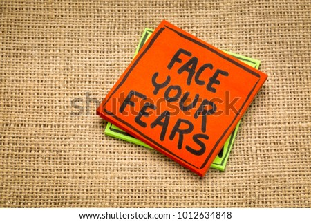 face your fears reminde - handwriting on a sticky note against burlap canvas #1012634848