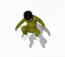 Faceless dark-haired little boy jumps on the background of a white wall in the studio. Child is dressed in a stylish green sports suit and white sneakers.