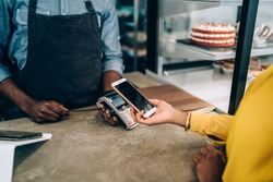 Faceless in yellow dress paying for order with mobile phone using payment terminal in cafe standing at counter with cakes and desserts