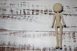 faceless knitted human figure on wooden background
