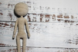 faceless knitted human figure on wooden background close up