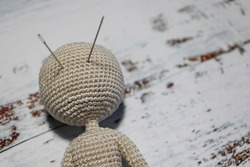 faceless knitted human figure on wooden background with needles instead of eyes