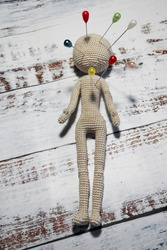 faceless knitted human figure studded with colorful knitting pins - illustration of social problems