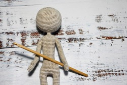 faceless knitted human figure with knitting needle on wooden background