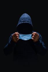Faceless man in dark blue hoodie putting on blue surgical mask, face hidden in shadow, darkness around him