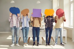Faceless people sharing message or expressing opinion in anonymous survey. Group of unrecognizable young college or university students covering faces with multicolored paper mockup speech bubbles