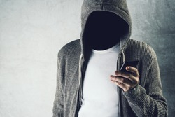 Faceless unrecognizable hooded person using mobile phone, identity theft and technology crime concept, selective focus on body