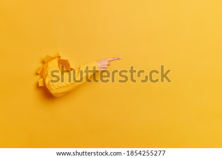 Faceless woman breaks arm through paper yellow wall indicates on right at blank space gives advice to buy subscription suggests to click on link shows direction. Place for your advertisement