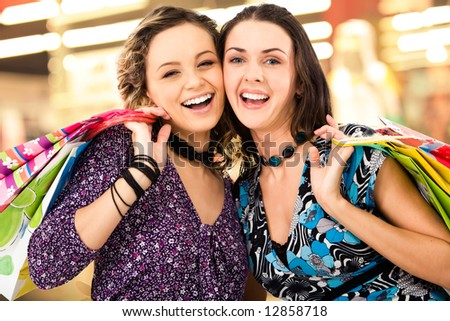 Faces of cheerful ladies in the shopping mall looking at camera amd laughing