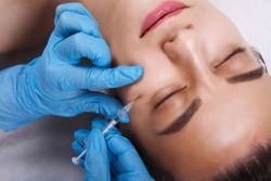 Facial Beauty Injections. Portrait Beautiful Young Woman Receiving Hyaluronic Acid Injection. Closeup Of Hands In Gloves Holding Syringe Near Attractive Female Face.