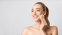 Facial Beauty Treatment. Happy Young Lady Using Cotton Pad Cleaning Face Looking Aside Over Gray Studio Background. Panorama, Free Space