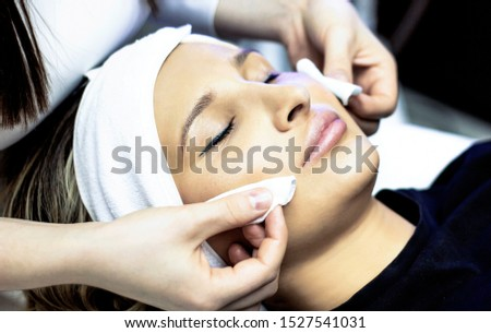 Facial cleansing procedure. Young woman enjoys radiant face in beauty salon, face skin care cosmetology, beautician, professional beautician, spa and freshness, clinic, concept #1527541031