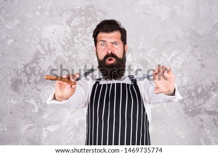 Facial hair. Bearded barber shaving. Barber tools. Barber in apron hairdresser equipment blade and scissors. Professional haircut. Barbershop master. Hairstyle concept. Grooming beard and mustache.