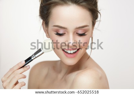 Facial Makeup. Closeup Of Beautiful Young Female Model Putting Blush With Cosmetic Brush. Portrait Of Attractive Healthy Girl With Pure Clean Skin And Natural Make-Up. Beauty Concept. High Resolution #652025518