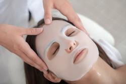 Facial mask. Cosmetologist applying facial mask sheet on womans face