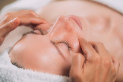 Facial massage beauty treatment. Close-up of a young woman's face lying on back, getting face lifting massage, pinch and roll technique.