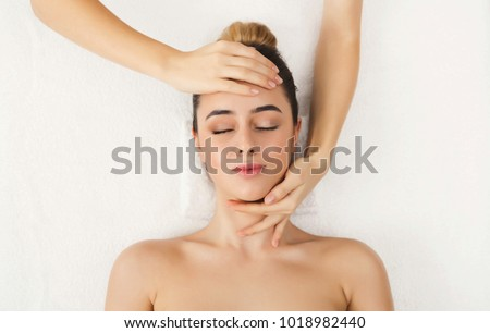 Facial massage. Spa, resort, beauty and health concept. Beautiful woman getting professional face treatment, top view, copy space