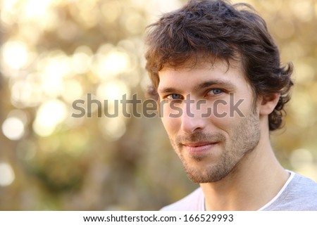 Facial portrait of an attractive adult man with an unfocused warm background