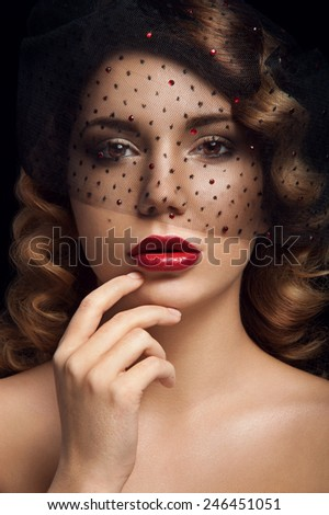 Facial portrait of lady with brown eyes, deep red lipstick, two nevus on her left cheek, curly hair and veil with black dots and rubies. Touching her lips. Black background.