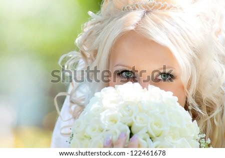 Facial portrait of the bride with a wedding bouquet