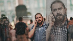 Facial recognition and search and surveillance of a person in the modern digital age, the concept. man with phone in crowd of people on the street, identification and modern technology