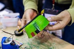 Facilitator fixing a trash robot . STEM Education activity with motors, feltpen, led and batteries.