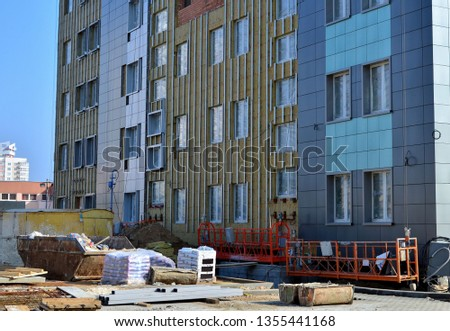 Facing and insulation of the building ventilated facade. Aluminum colored facades. Modern facades of high-rise buildings. Construction of a large shopping business center.  #1355441168