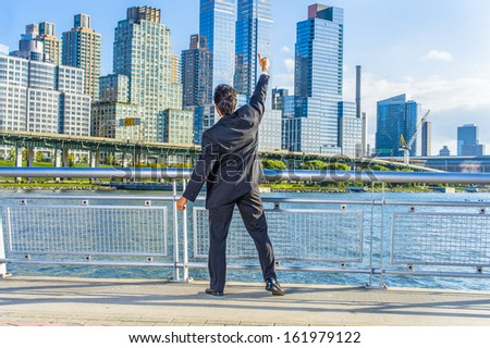 Facing dramatic high buildings of New York City, a middle age businessman is raising his arm and thumb up, a symbol of success. / Thumb Up