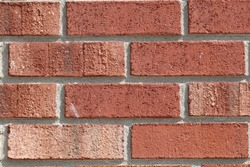 Facing masonry, in light red-brown tones. Four rows of masonry, with rectangular recessed seams. For textures, wallpapers and backgrounds.
