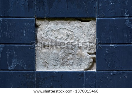 Facing plates on the wall of the building. Two Central tiles fell off. Rectangular tiles. In the center of the a grey squaring, on the edges of the the dark edging.