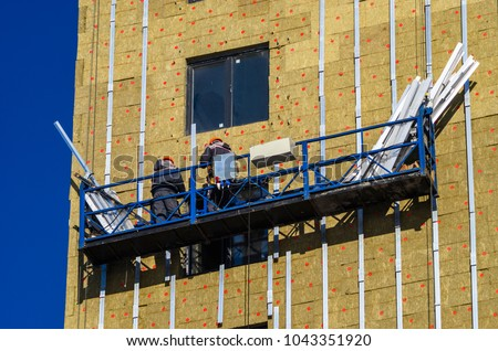 Facing the building with a ventilated facade. Aluminum colored facades. Modern facades of high-rise buildings. Construction of a large residential complex. Suspended construction cradle. #1043351920
