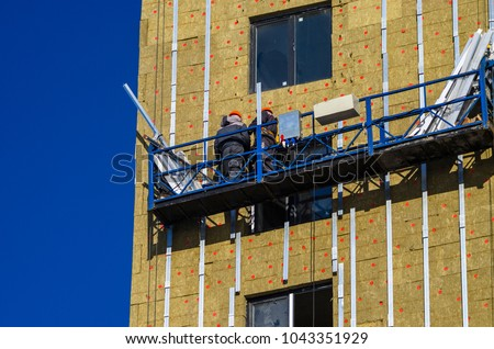 Facing the building with a ventilated facade. Aluminum colored facades. Modern facades of high-rise buildings. Construction of a large residential complex. Suspended construction cradle. #1043351929