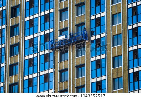 Facing the building with a ventilated facade. Aluminum colored facades. Modern facades of high-rise buildings. Construction of a large residential complex. Suspended construction cradle. #1043352517