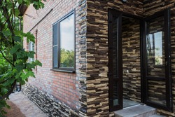 Facing the facade of a private house with a decorative stone. Content construction.