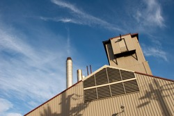 Factory building and chimney with a cloud like smoke early in the morning against a dramatic blue sky.