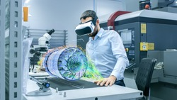 Factory Chief Engineer Wearing VR Headset Designs Engine Turbine on the Holographic Projection Table.  Futuristic Design of Virtual Mixed Reality Application.