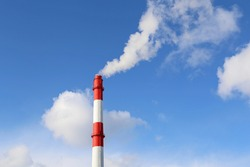 Factory chimney on blue sky and clouds background with white smoke. Concept of steam plant, air pollution, heating season