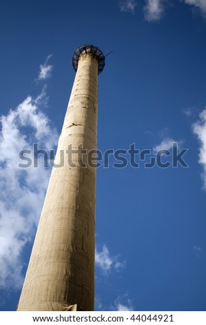 Factory chimney on the blue sky background