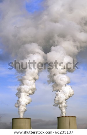 Factory chimneys smoke in the background of blue sky.