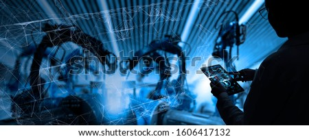 Factory Female Industrial Engineer working with automation robot arms machine in intelligent factory industrial on real time monitoring system software.Digital future manufacture.