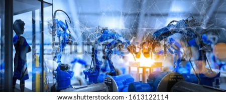 Factory Female Industrial manager Engineer looking at automation robot arms machine in intelligent factory industrial on real time monitoring system software.