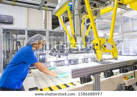Factory floor worker coating glass for solar panel assembly on production line
