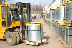 Factory Forklift Truck Stacker Transporting Roll of Transformer Steel at Electrical Plant Warehouse