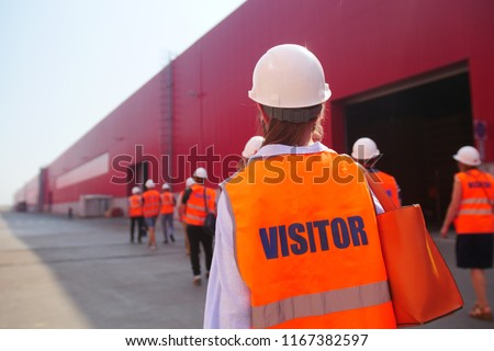 factory inspection. group of visitors on the factory tour. people go in helmets and uniforms for an industrial enterprise