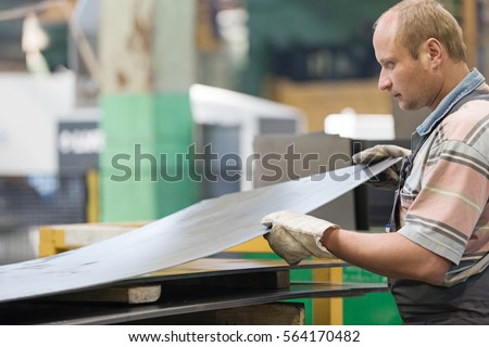 Factory Man Worker Holding Metal Sheet in Workshop during Manufacturing Process