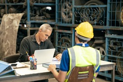 Factory manager looking at the paper with young engineer sitting front for call for blaming or consider and interview job apply or solving working problem report situation at factory work