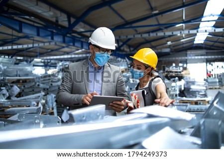 Factory manager with face protection mask visiting production line and discussing with worker about efficiency or production deadline. Industrial health measures during corona virus pandemic. Foto stock ©