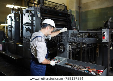 Factory master pressing button on panel of industrial machine during work #758139586