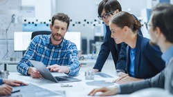 Factory Meeting Room: Multi-Ethnic and Diverse Team of Engineers, Managers, Investors Talking Sitting at Conference Table, Analyzing Blueprints, Mechanism Component. High-Tech Manufactory Optimization