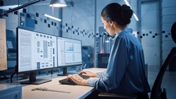 Factory Office: Portrait of Beautiful and Confident Female Industrial Engineer Working on Computer, on Screen Industrial Electronics Design Software. High Tech Facility with CNC Machinery